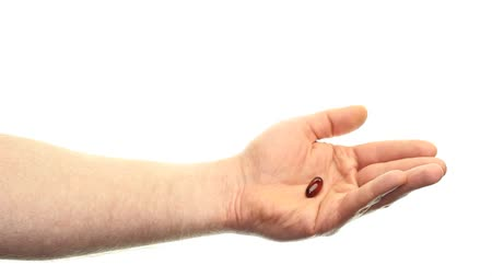 fatty acid : Caucasian hand showing one dose of a flaxseed oil soft gel supplement in front of a white background, moving around a little and then withdrawing hand to the left.