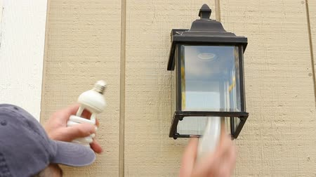 régi : Man outside changing an incandescent light bulb to a CFL light bulb in a light fixture to save energy. Stock mozgókép