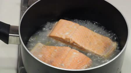 somon : Two wild sockeye salmon fillets poaching in some boiling water in a pan on a gas stove top.