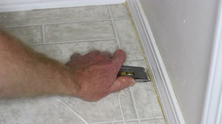 opravář : Hand and arm with a cutting tool stripping away old, yellowed caulk around a linoleum floor baseboard.