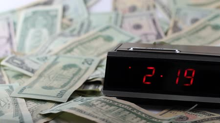 esquerda : Fast Clock with Still Money.  A red numbered digital clock with a browse button moves the time display rapidly while a variety of American dollars lays on a white background on the left and in front Stock Footage