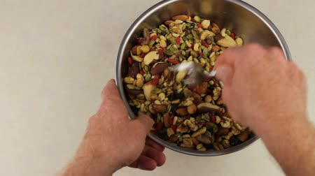 garfos : Hands With Fork Mix Nuts and Fruits. Adult male hands mixing a wide assortment of organic, gourmet dried fruits, nuts and seeds with a fork in a large round stainless steel bowl on a counter.