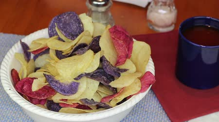 três quarto comprimento : Fingers Choosing Colorful Potato Chips Male fingers picking up one at a time, red white and blue potato chips variety. Crimson, yellow and purple potato chips in a bowl being picked up individually.