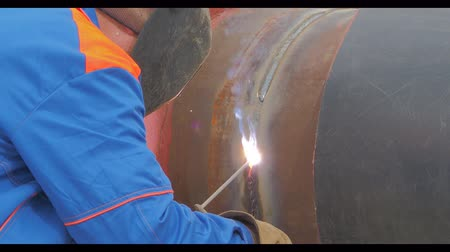 angle grinder : a worker performs welding of metal pipe