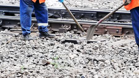 pneumatic : Railwayman in uniform with shovel in hands repairs railway track. Stock Footage