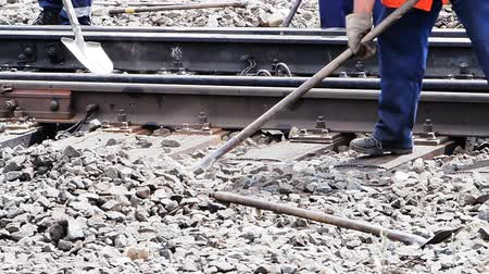 Railwayman in uniform with shovel in hands repairs railway track. Stock Footage