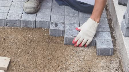 constructing : a man lays paving slabs on a pedestrian street. Stock Footage