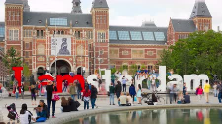 amsterodam : AMSTERDAM, NETHERLANDS - JULY 14, 2015: People walk near Rijksmuseum on the Muzeumpleine in Amsterdam, one of the main focal points of the city.