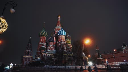 urss : Red Square, a lonely guy walks past the Kremlin and Basil Church, winter, night