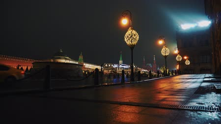 urss : Red Square, few taxi cars drive past the Kremlin and Basil Church, winter, night