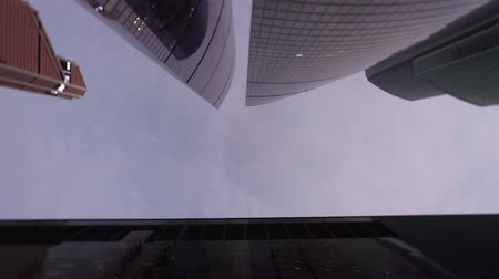 Panning view from below of the office tower buildings with vertical rotation