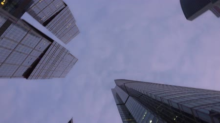 perspective : Modern skyscrapers of unusual shape, made of glass. Bottom up view with rotation