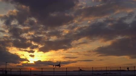futópálya : Plane is landing. Dawn. Early morning. The sky is orange on the horizon