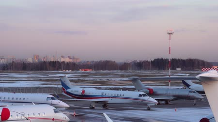 Large number of airplanes parked at the airport. Business jets passengers planes