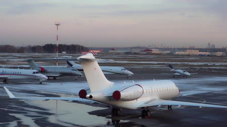 Five small and medium-sized business jets parked at the airport. Winter snow. 4K