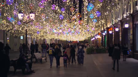 barbante : Busy pedestrian street. Large number of walking people, Christmas lights, decor