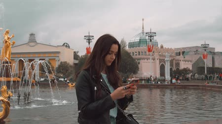 Young beautiful girl is typing message. Beautiful fountain in the background. 4K