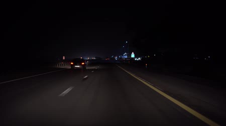nem városi színhely : Driving a car on a night highway, point of view. lights of the city are visible