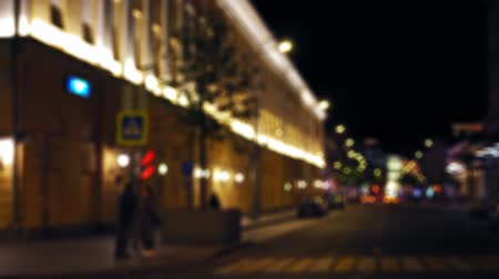 маркировка : Defocused view of the night city street. Cars drive along the road. People walk