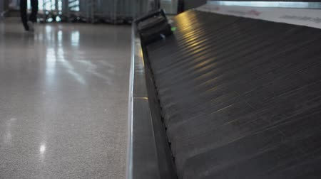 concourse : Two suitcases brown and black, are approaching on a conveyor belt at the airport