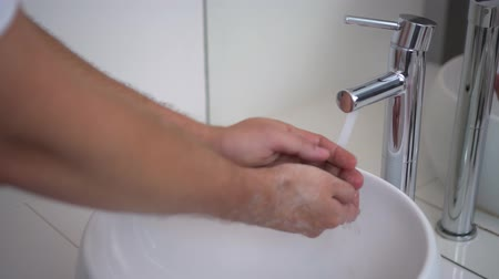 lavabo : Man washes his hands, closeup view. Bathroom, white modern washbasin, chrome tap