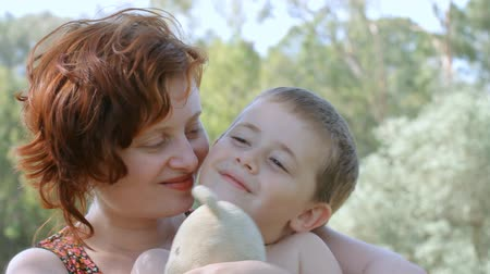 объятие : Happy smiling young boy with toy together with mother.