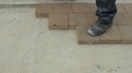 kielnia : Worker laying brick tiles on the road Wideo