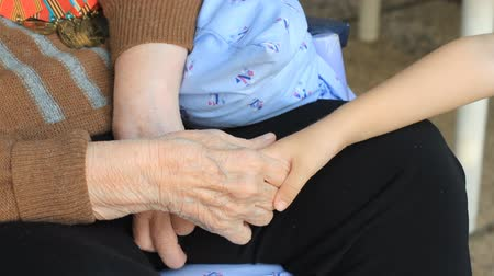 veterano : Grandmother holds the hand of his grandson
