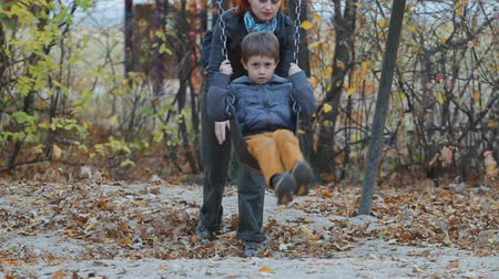 ailelerin : Mom Pushing her son on a swing in a park in autumn Stok Video