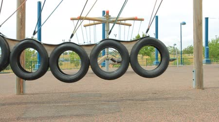 plac zabaw : Swing from car wheels in the motion on the playground