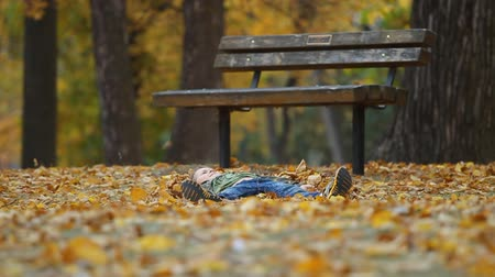 felicidade : Seven year old boy throws autumn leaves and running