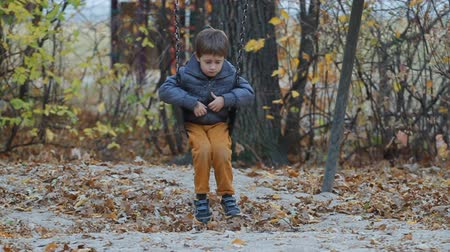 üzgün : Very sad and cute boy sitting on a swing in a park in autumn Stok Video