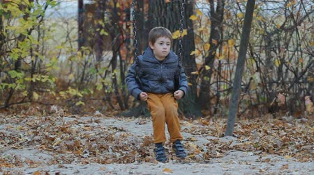 yalnız : Very sad and cute boy sitting on a swing in a park in autumn Stok Video