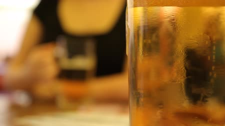 алкоголизм : Beer into a glass and woman drinking beer on background. Side of Glass beer with bubbles