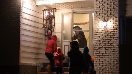 trik : Three children with family in Halloween costumes trick or treating Dostupné videozáznamy