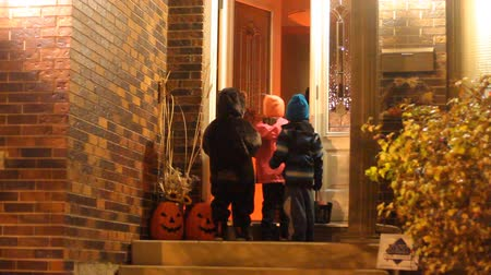 trik : Three children in Halloween costumes trick or treating