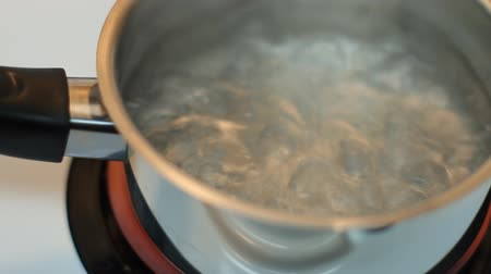 fogão : Pot full of boiling water on the electric stove.