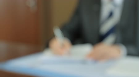 подпись : Anonymous businessman fills an application form. Unfocused shot background