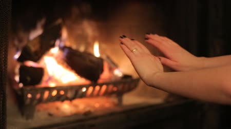 ailelerin : Woman warming her hands by the fireplace