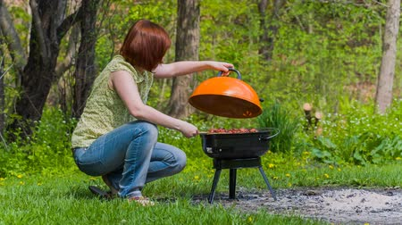 piknik : Young woman grilling liver in the park in summer Stok Video