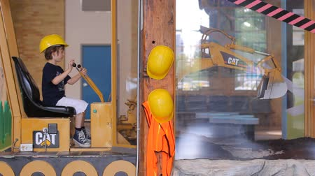 juventude : Boy in yellow builder helmet sitting in simulator of excavator and playing with joystick