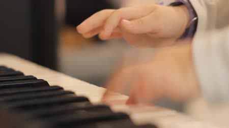 lesson : Close up of two childs small hands playing piano Stock Footage