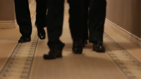 cipőfűző : Four pairs of mens feet walking on carpet in black shoes
