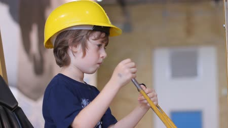 музей : Kid in yellow builder helmet sitting in simulator of excavator and playing with joystick