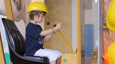 earthworks : Boy in yellow builder helmet sitting in simulator of excavator and playing with joystick