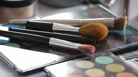 Make-up brushes laying on colorful cosmetic palette Стоковые видеозаписи