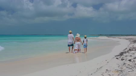 Young family walking together at tropical beach in Cayo Largo island