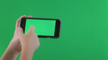 мобильный телефон : Closeup of child hands using a smart phone. Chroma key, green screen