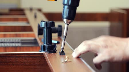 folheado : Master joinery installs the attachment for the furniture legs on the workpiece Vídeos