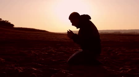 dua eden : Silhouette of a man praying at sunset concept of religion Stok Video